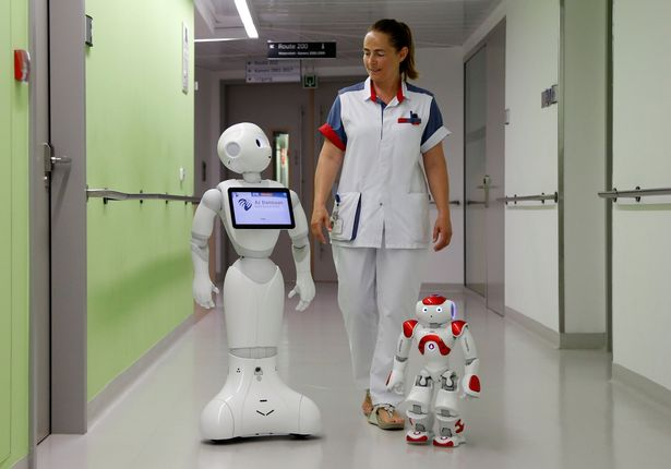 A-nurse-walks-with-Pepper-L-and-Zora-the-robots