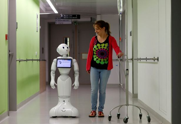 A-woman-walks-with-new-recruit-Pepper-the-robot
